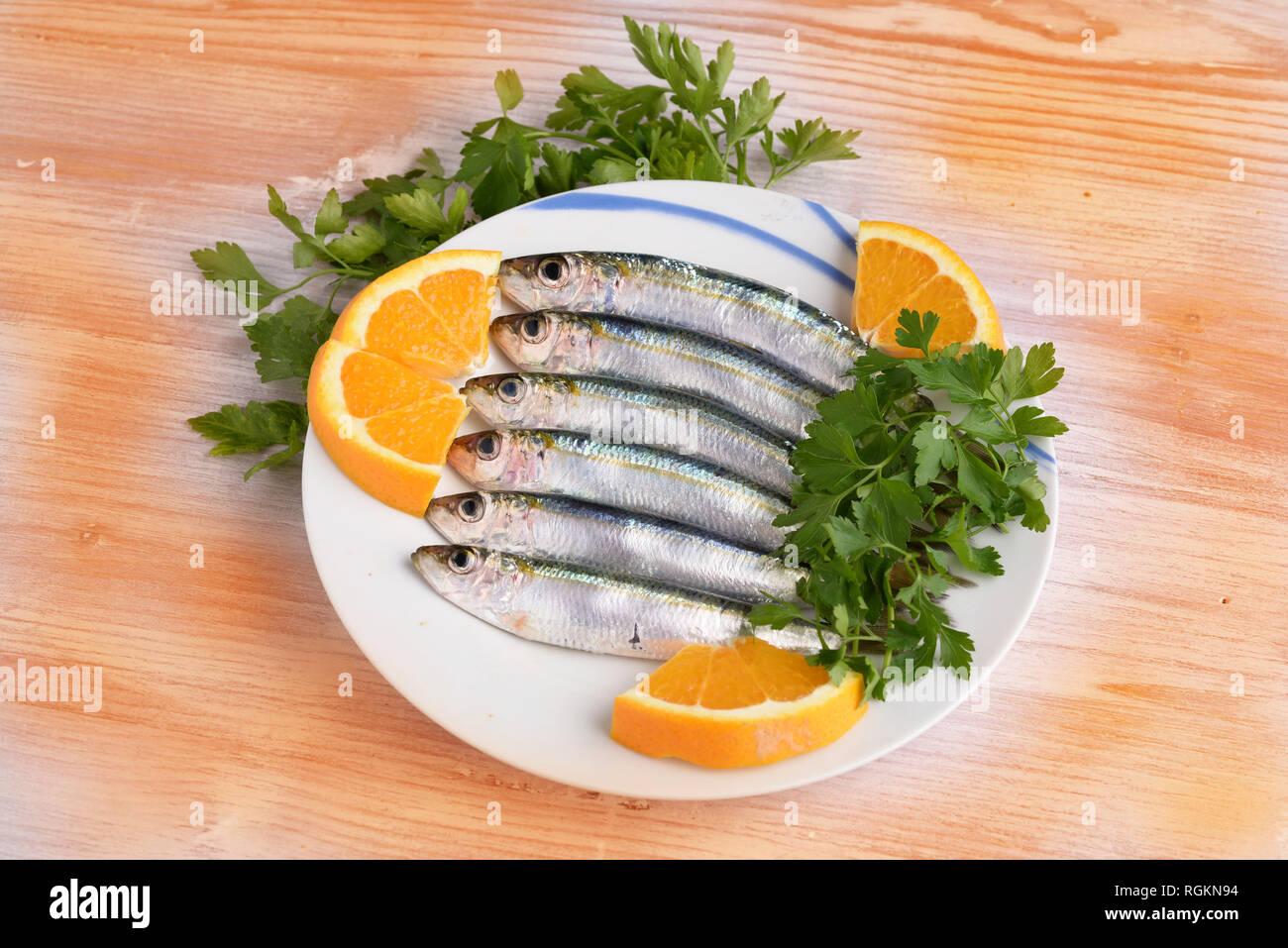 Sardinen mit Zitrone und Petersilie auf Teller mit Holz- Hintergrund farbig Stockbild