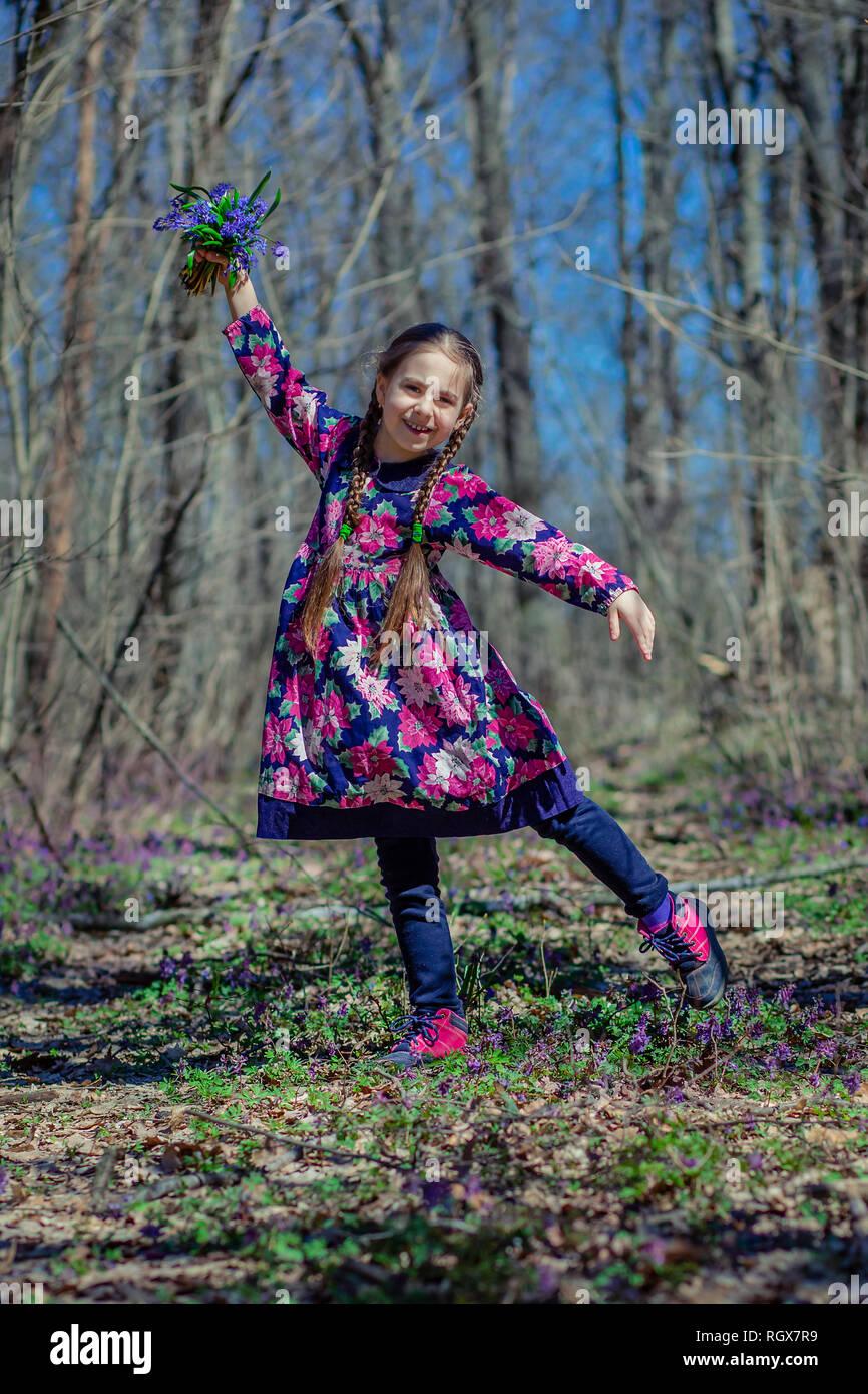Porträt einer wunderschönen kleinen Mädchen mit corydalis Blumen. Wandern im Frühjahr Wald an einem sonnigen Tag. Stockfoto