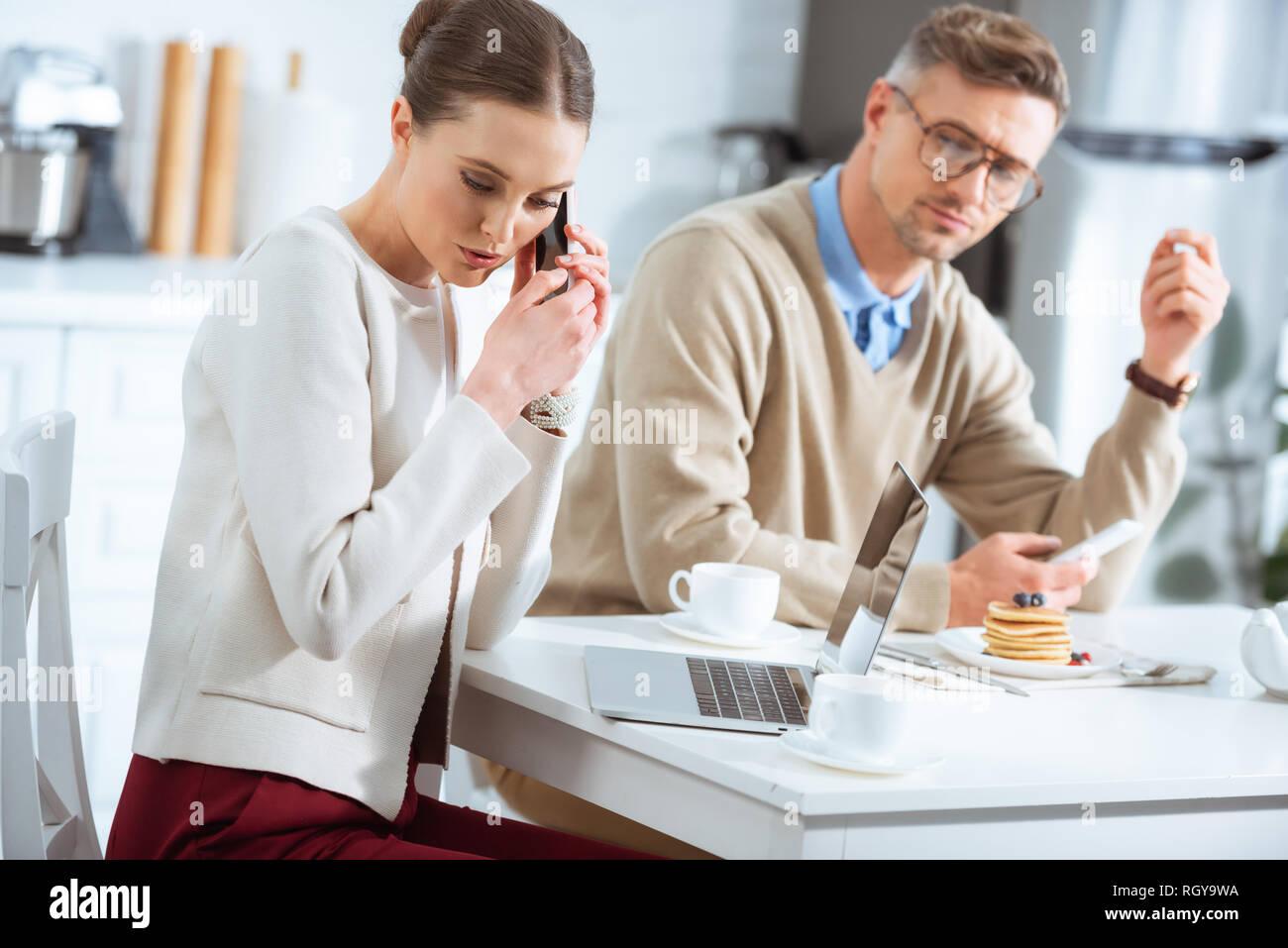 Mann an Frau heimlich Reden auf dem Smartphone beim Frühstück suchen Stockbild
