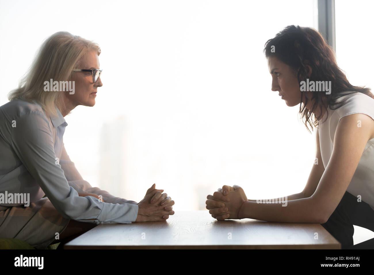 Jung und Alt Geschäftsfrauen gegenüber sitzt, Generationen Konflikte am Arbeitsplatz Stockbild
