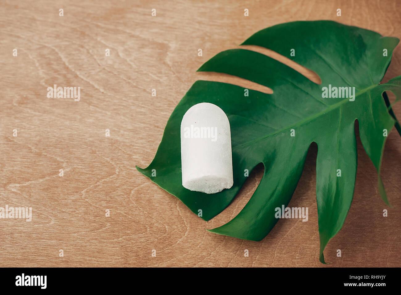 Nachhaltiger Lebensstil. Natürliche eco crystal Deodorant anulit auf hölzernen Hintergrund mit grünen monstera Blatt. Kunststoff freie Schönheit Essentials. Null Abfall Stockbild