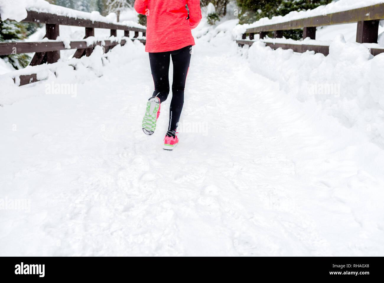 Junge Frau läuft auf Schnee im Winter Berge tragen warme Kleidung Handschuhe im Schnee Wetter. Sport, Fitness Inspiration und Motivation. Gerne jugendlich nicht Stockfoto