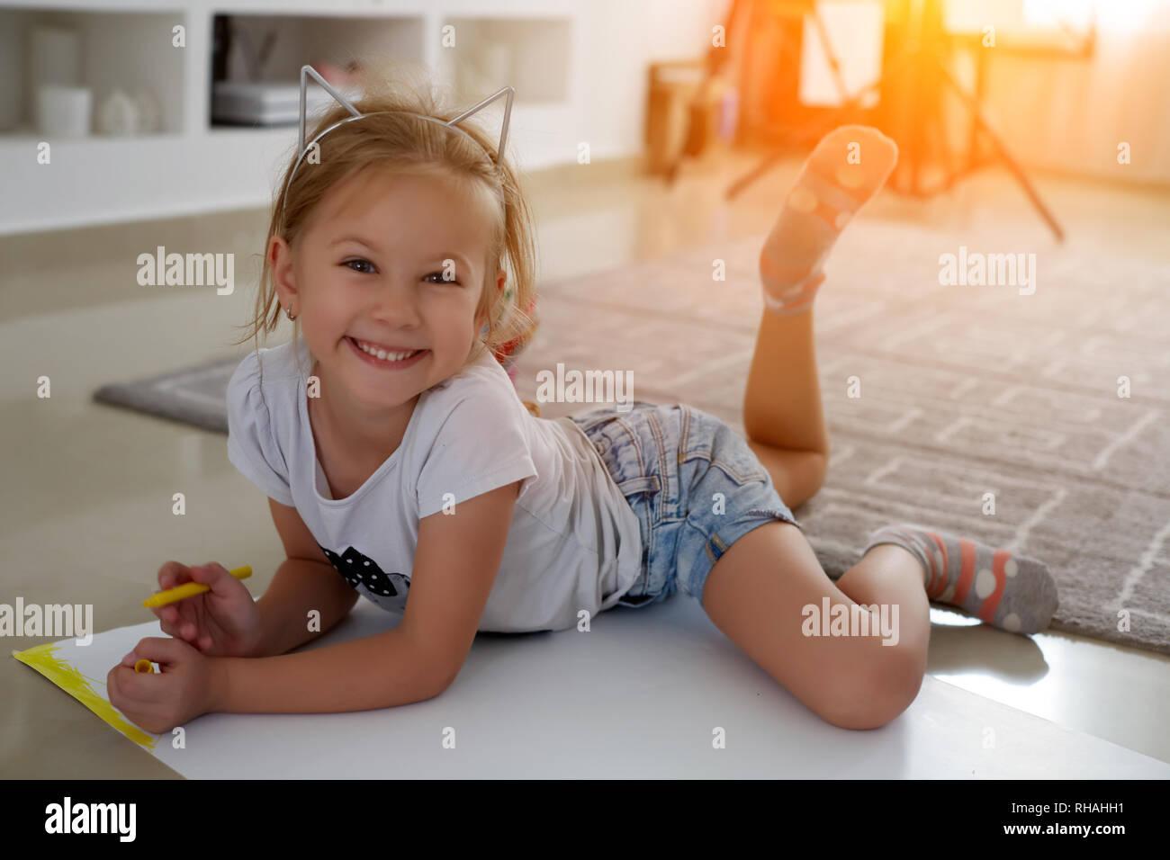 Glückliches Kind. Foto betrachten Seite kreative Mädchen liegen in der Nähe der Bücher und Spielwaren, Zeichnen Stockfoto