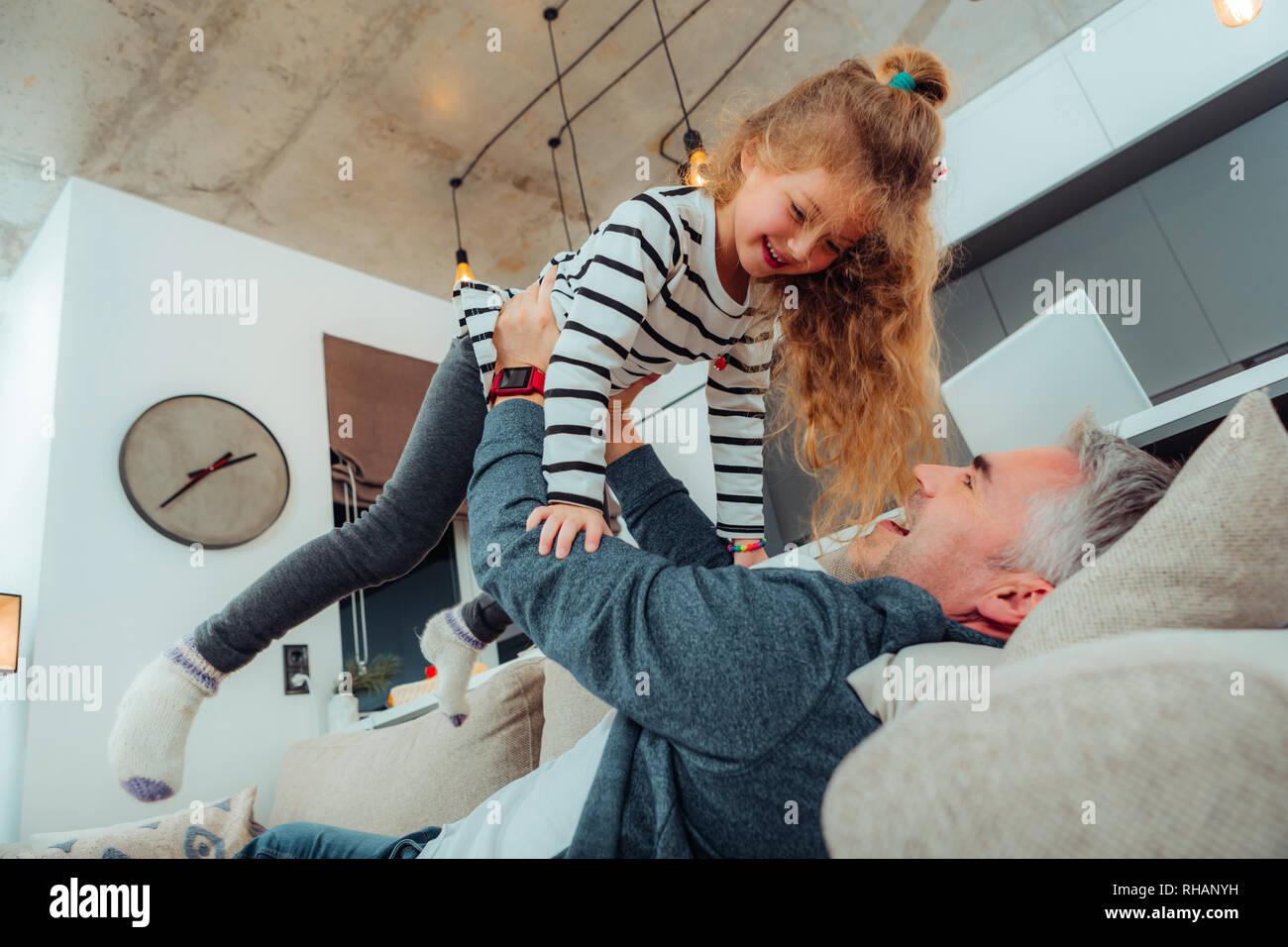 Süße kleine Tochter in einem gestreiften Pullover Gefühl zufrieden Stockbild