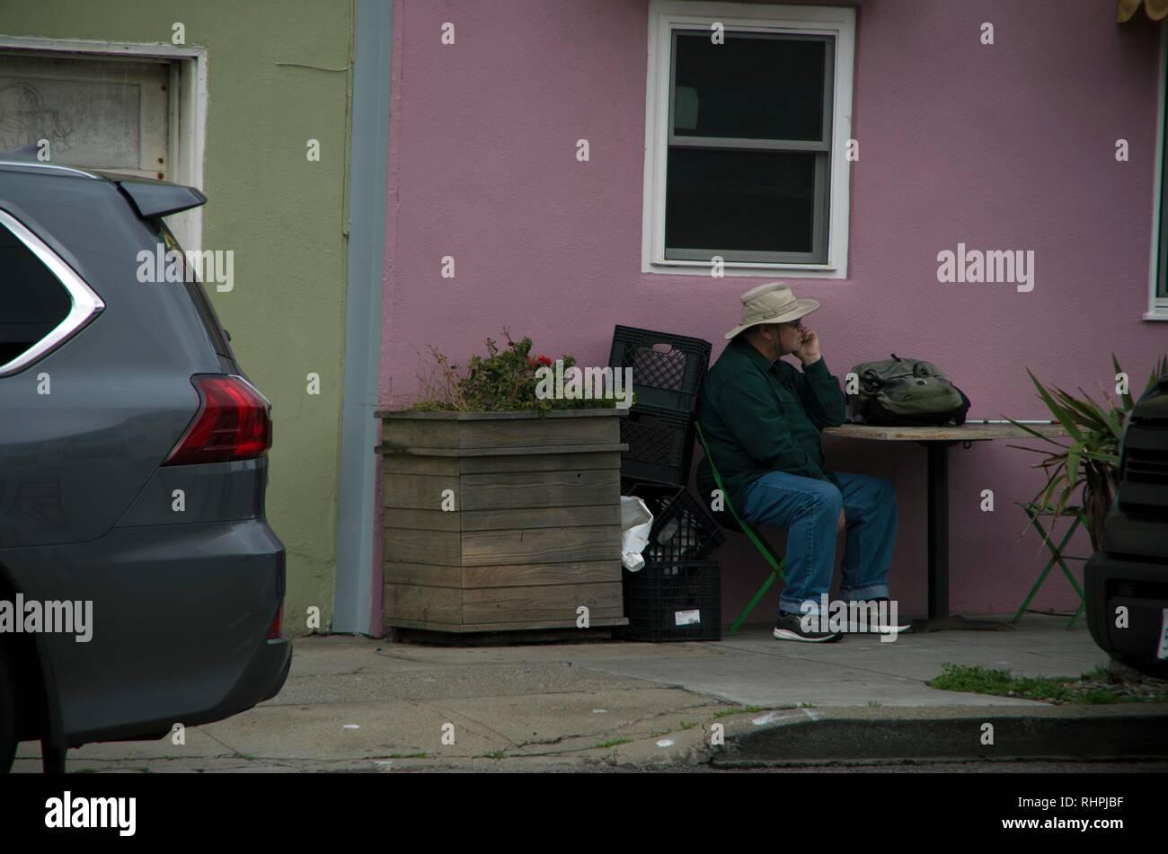Ein Mann sitzt allein in einem Café in der Nähe von Ocean Beach in San Francisco, vielleicht darauf warten, dass jemand ihn zu verbinden. Stockbild