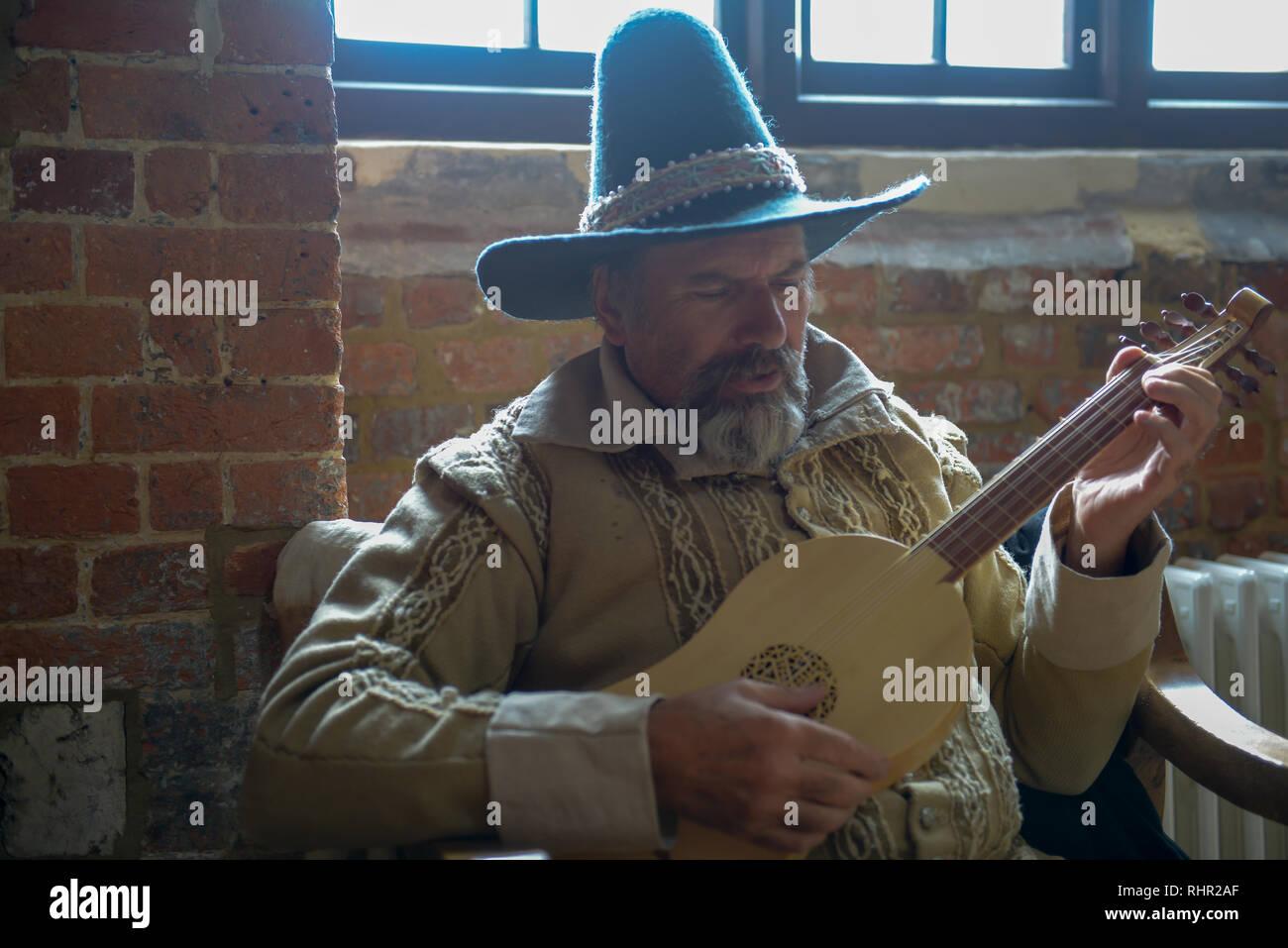 Alter Mann im historischen Kostüm spielen Laute Stockbild