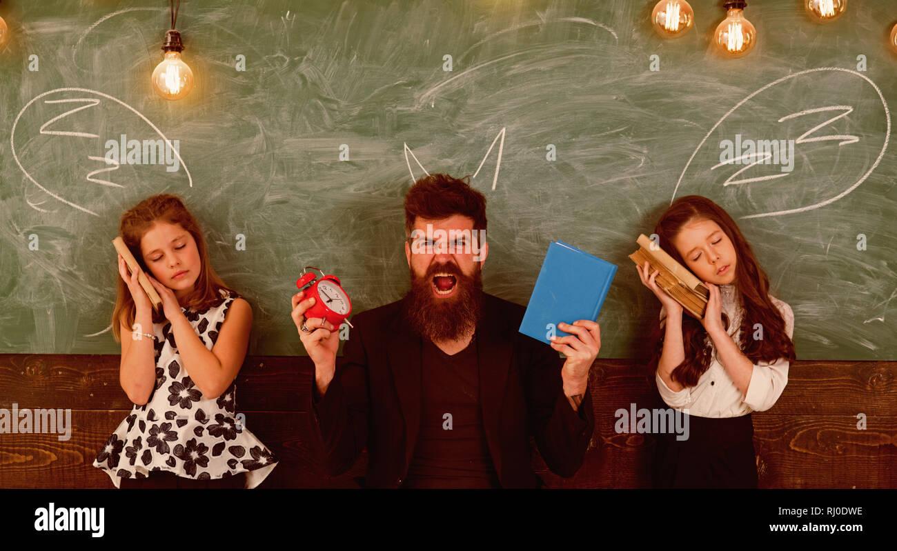 Lehrer und Schüler Mädchen im Klassenzimmer, schwarzes Brett für den Hintergrund. Kinder und Lehrer und gezeichnet von Chalk Hörner. Schreckliche Lektion Konzept. Mann mit Stockbild