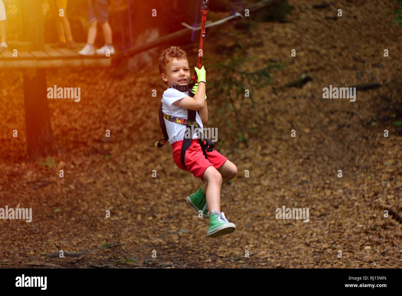 Klettergurt Mit Helm : Glückliches kind mit helm und klettergurt auf zip line zwischen