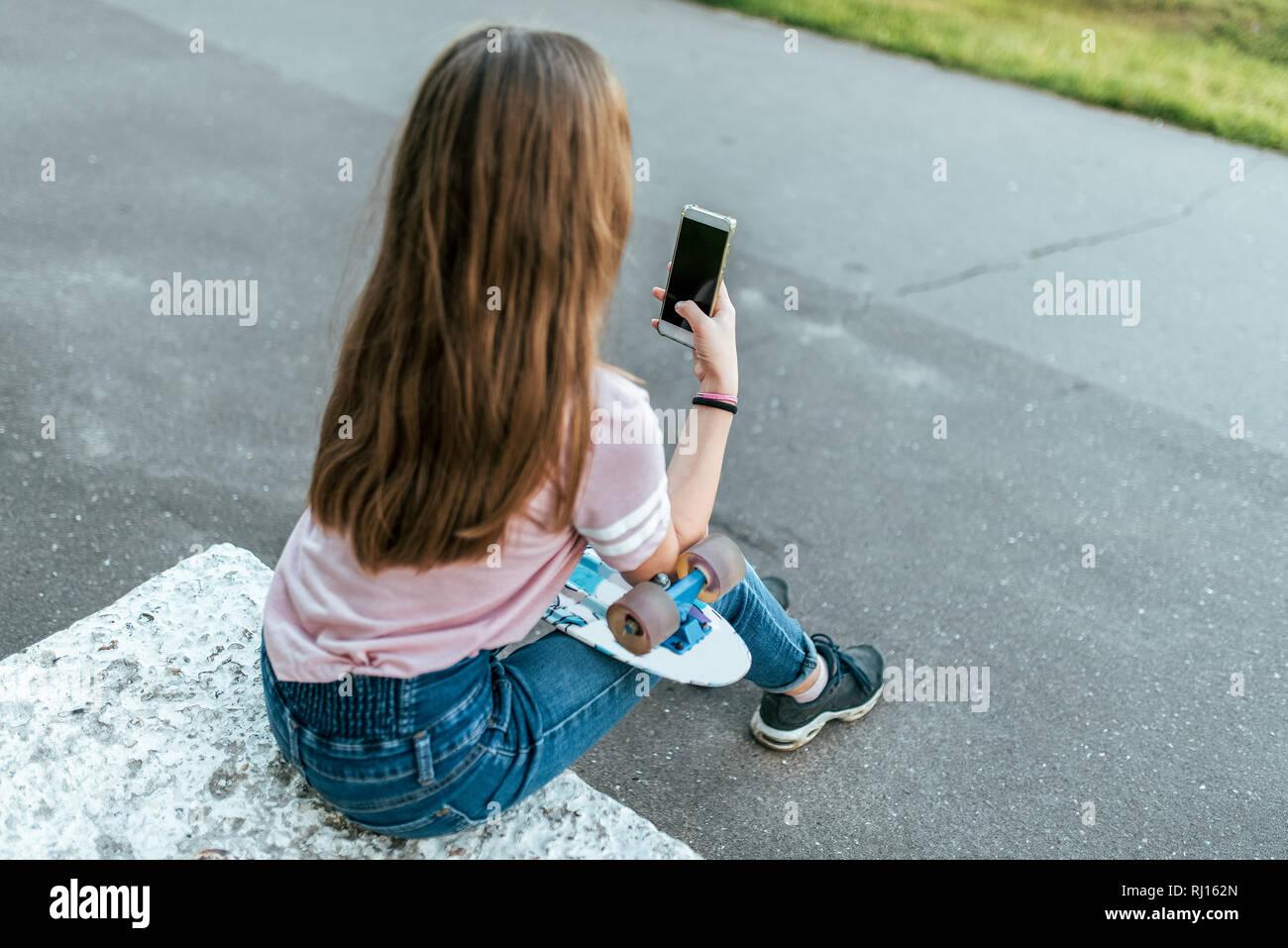 Jugendlich Mädchen 9-10 Jahre alt und sitzt in Händen eines Skate. Im Sommer in der Stadt in lässigen Jeans. Kommunikation im Internet, in den Händen der Smartphone hält Stockbild