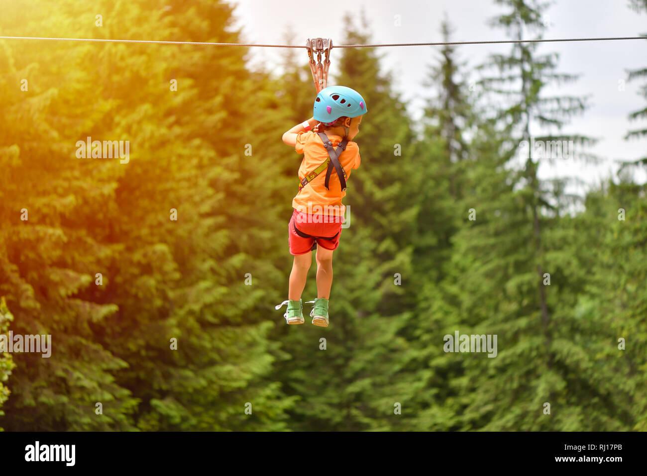 Klettergurt Baum : Glückliches kind mit helm und klettergurt auf zip line zwischen