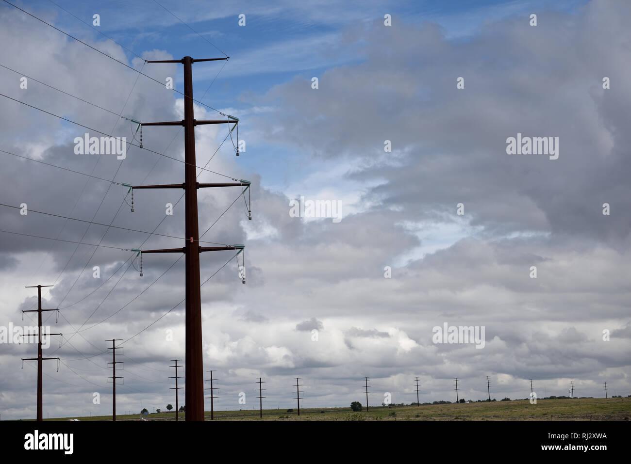 Reihe von Stahl Strommasten, Hochspannungsleitungen gegen einen stürmischen Himmel im Norden von Texas, USA. Stockbild