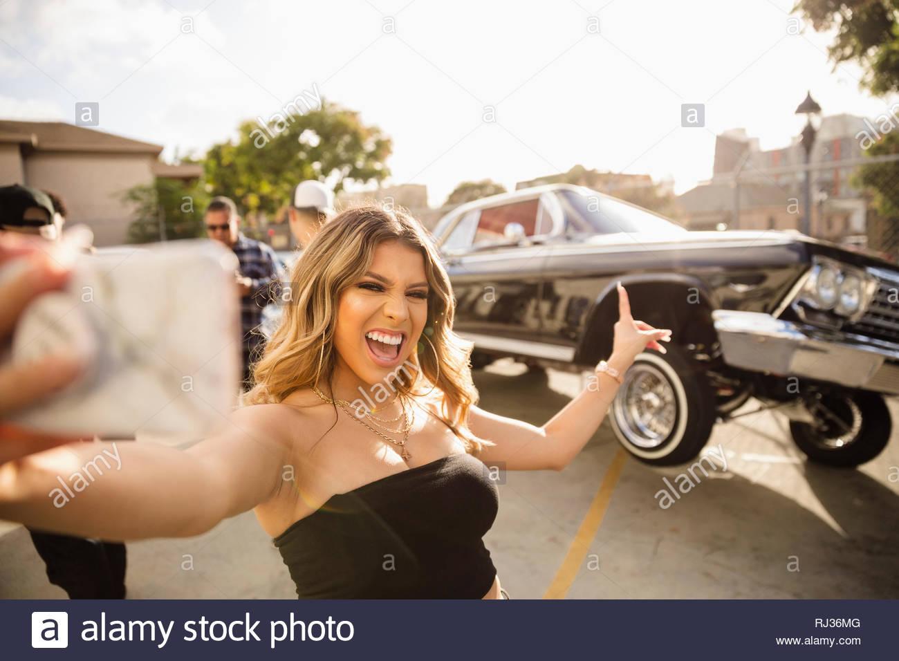 Selbstbewusst, begeisterte junge Frau, Latinx selfie vor Low Rider Auto springen in Parkplatz Stockbild