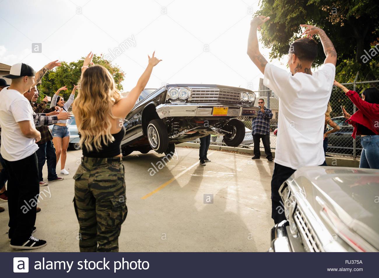 Latinx Freunden zujubeln, Low Rider Auto springen in Parkplatz Stockbild