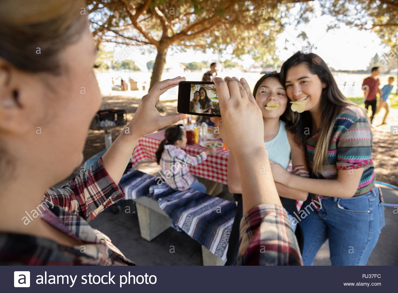 Frau mit Kamera Handy fotografieren verspielten Mädchen im Park Stockfoto