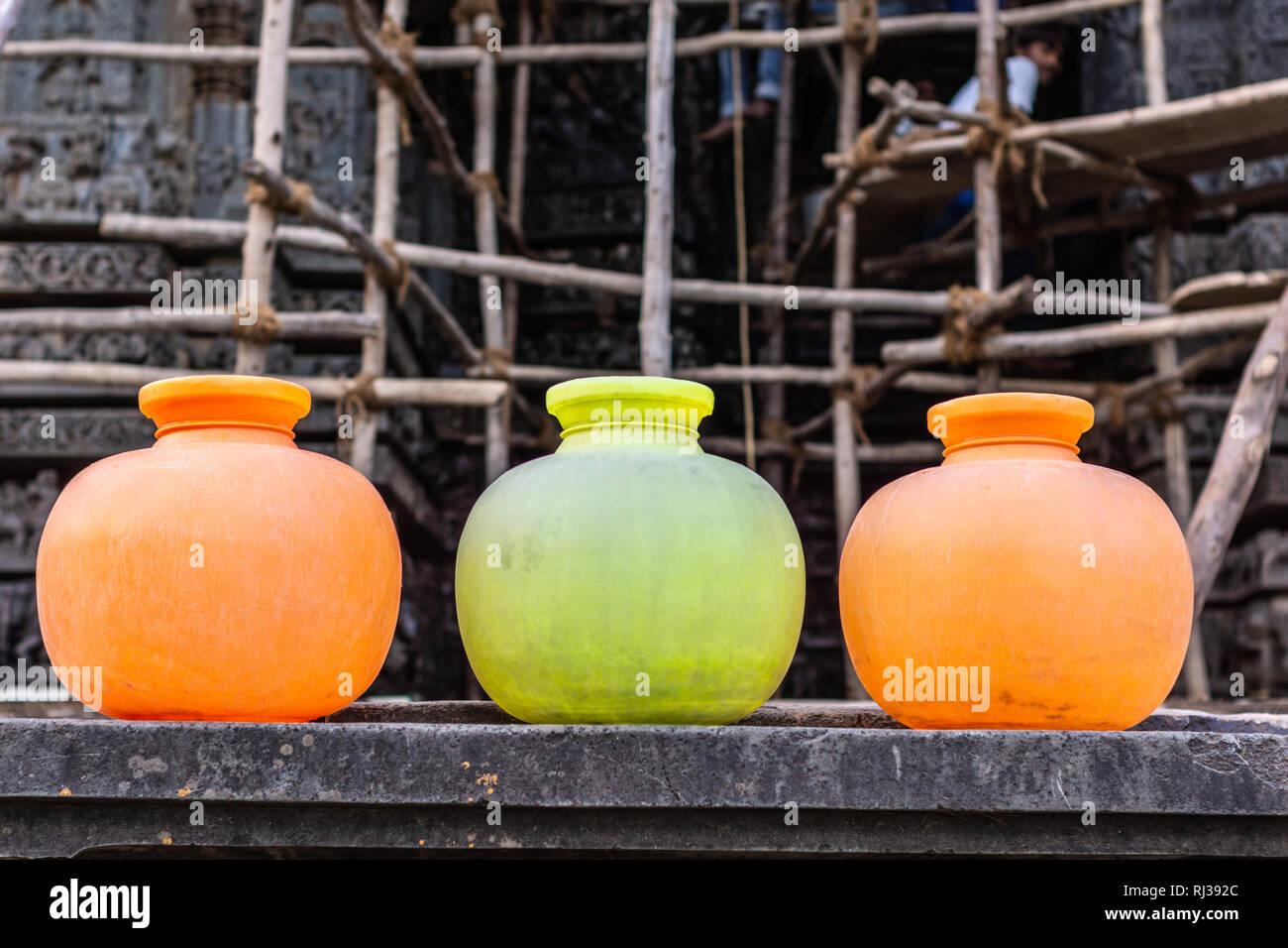 Halebidu, Karnataka, Indien - November 2, 2013: Hoysaleswara Tempel von Shiva. 3 Orange und Zitrone farbige Kugel wasser Behälter auf die Arbeitnehmer. B Stockbild