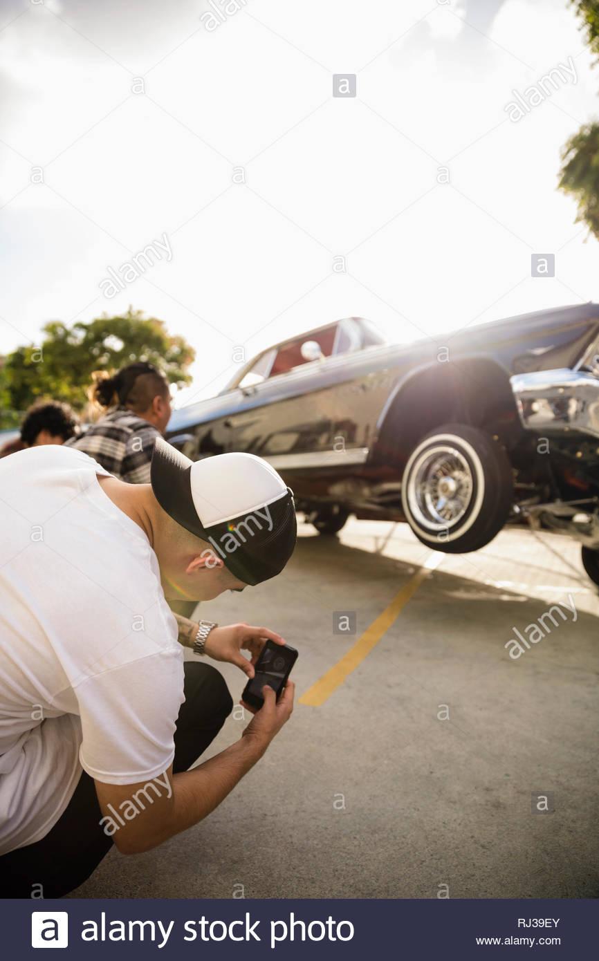 Latinx junger Mann mit Kamera Handy fotografieren Low Rider Auto springen in Parkplatz Stockbild