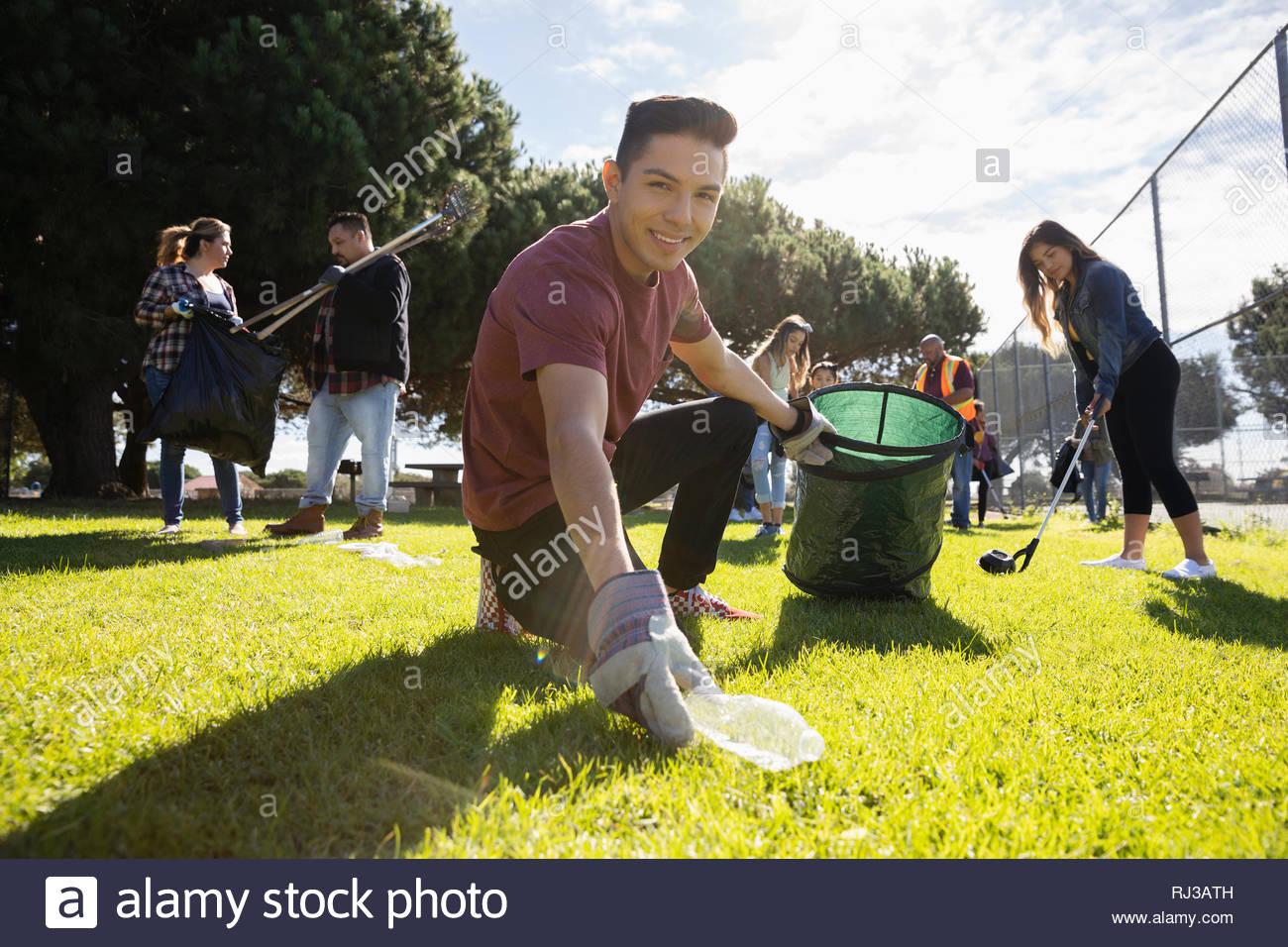 Portrait zuversichtlich Latinx jungen männlichen Freiwilligen Abholung Müll im sonnigen Park Stockbild