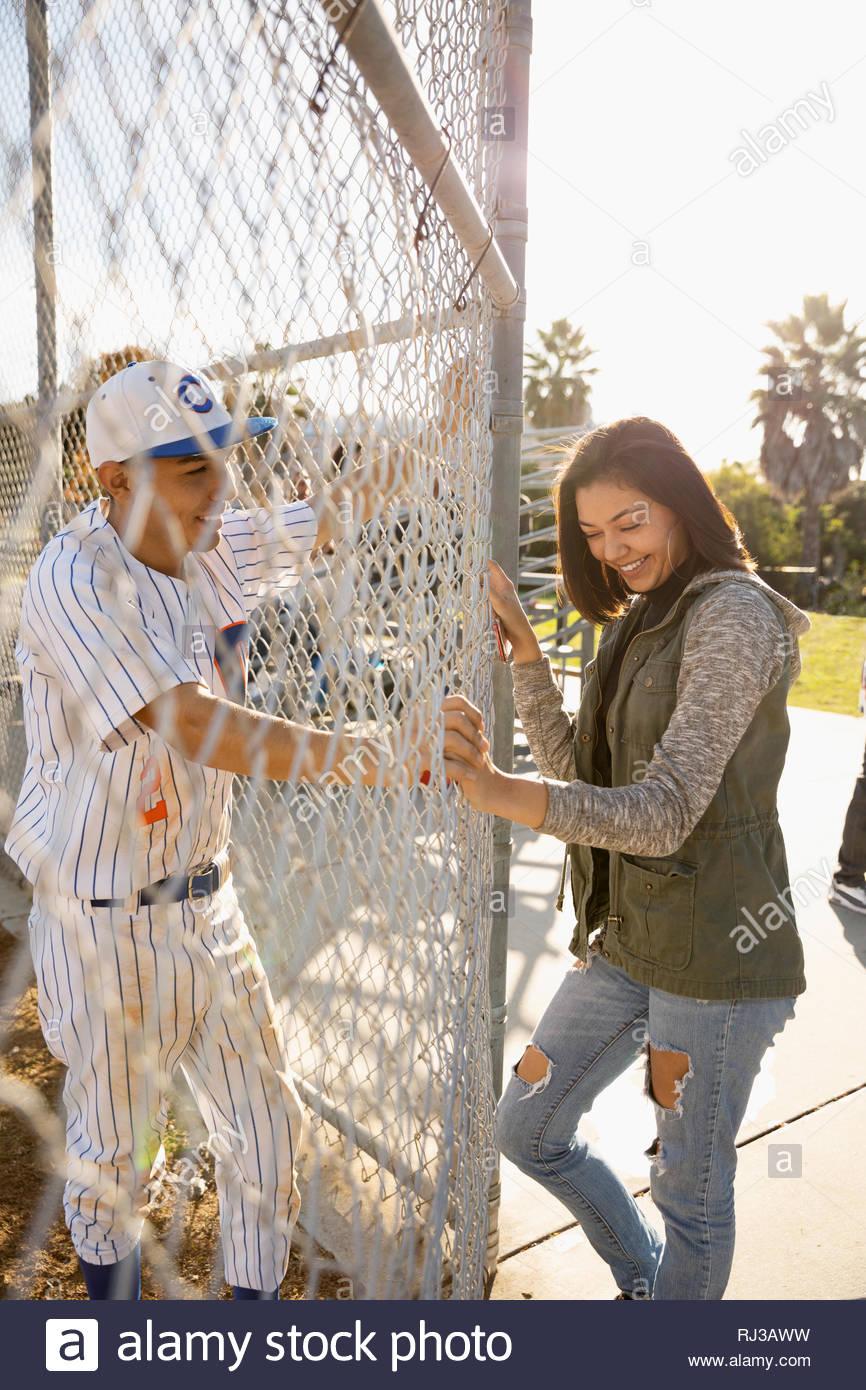Latinx Baseballspieler im Gespräch mit lächelnden Freundin am sonnigen Zaun Stockbild