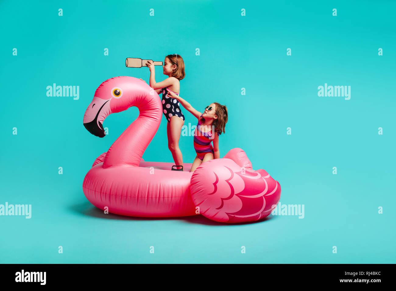Zwei mädchen spaß auf aufblasbaren spielzeug flamingo. kinder in