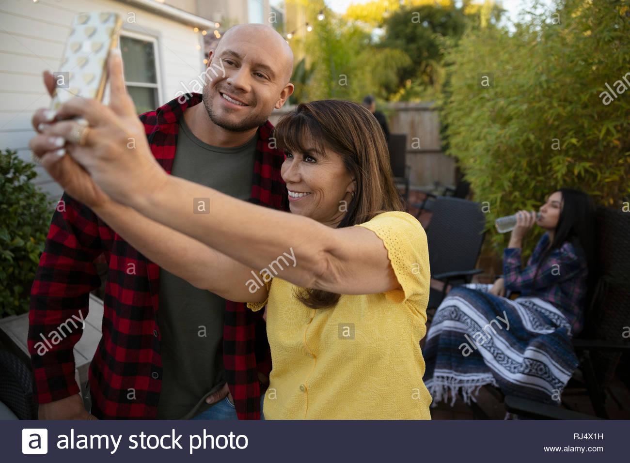Latinx Mutter und erwachsener Sohn selfie mit Kamera Handy Stockbild