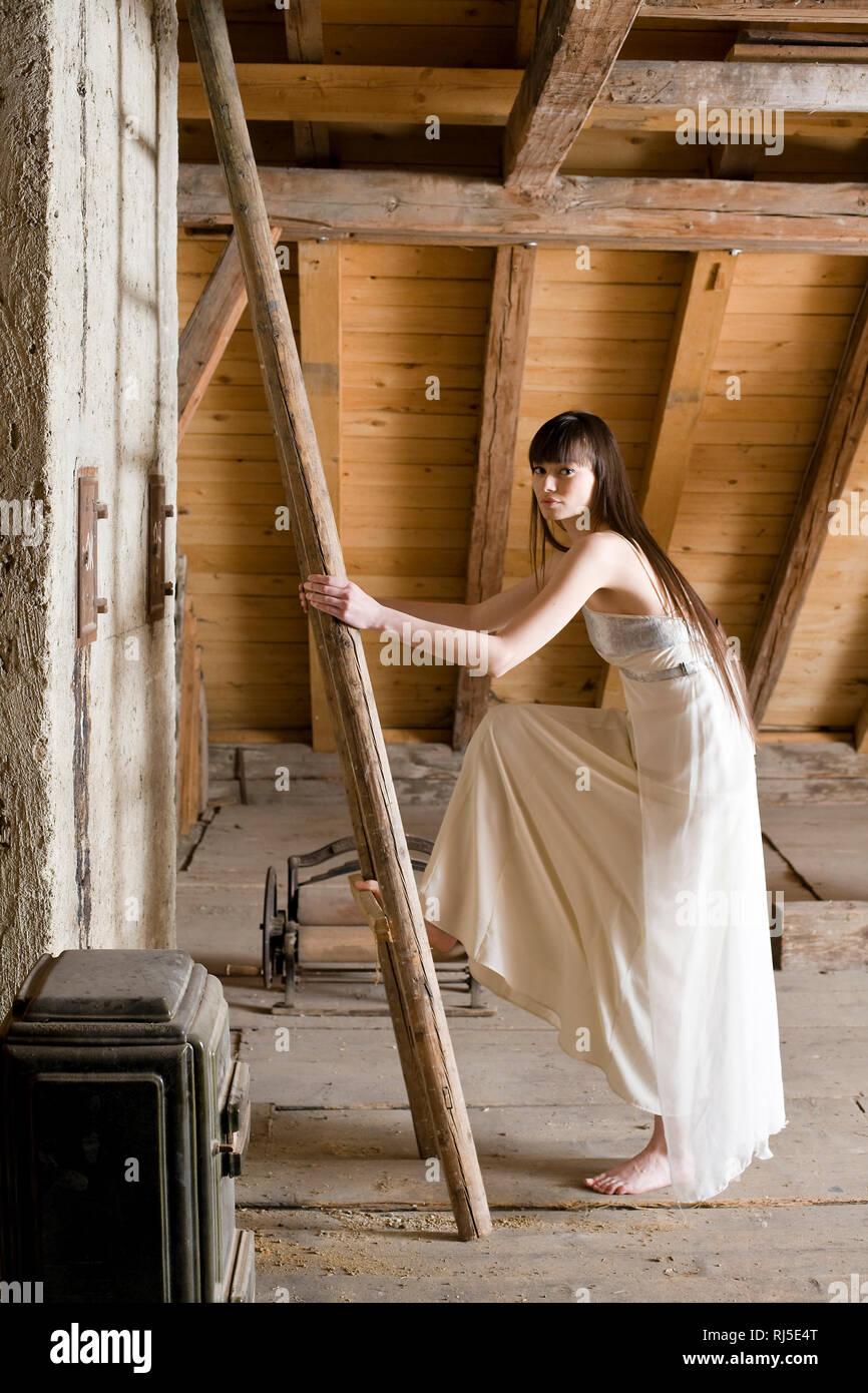 Frau e mit Abendkleid vor einer Leiter auf dem Dachboden Stockbild