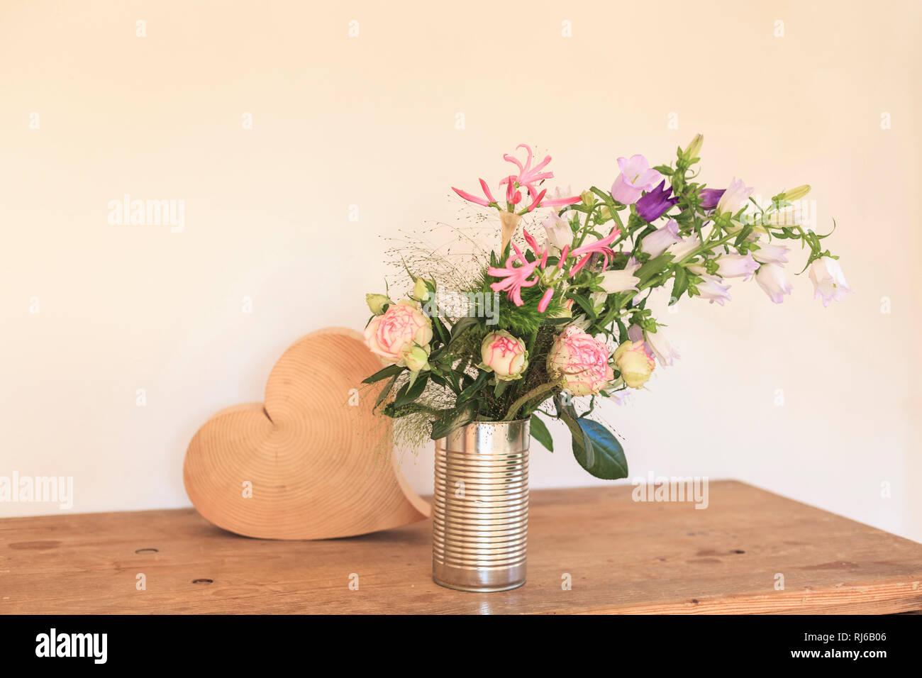 Strauß Sommerblumen, Dosis als Vase, daneben ein Herz aus Holz Stockbild