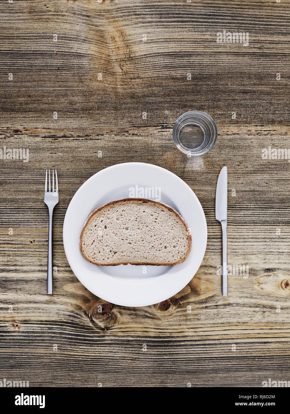 Eine Seine Brot auf Teller, Besteck und Glas in altem Holztisch, von Ihr Browser kann leider keine eingebetteten Frames anzeigen Stockbild