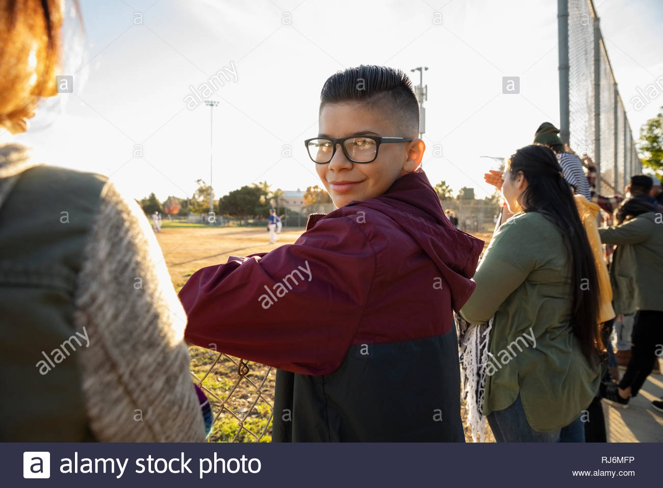 Portrait zuversichtlich Latinx Junge dem Baseball Spiel am Zaun Stockbild