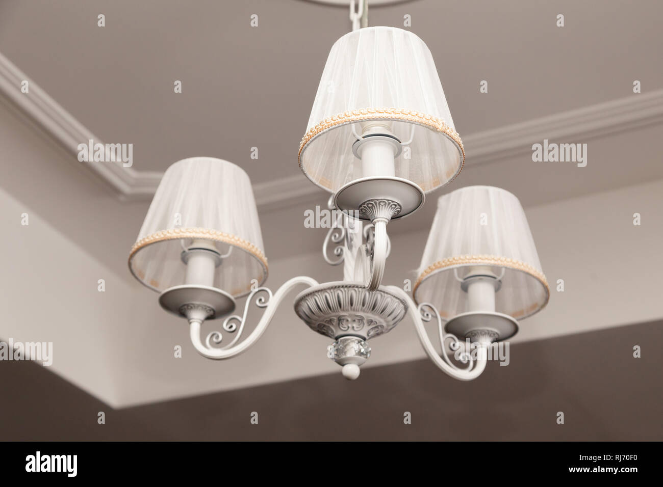 Kronleuchter mit drei elektrischen Lampen und Lampenschirme hängen ...