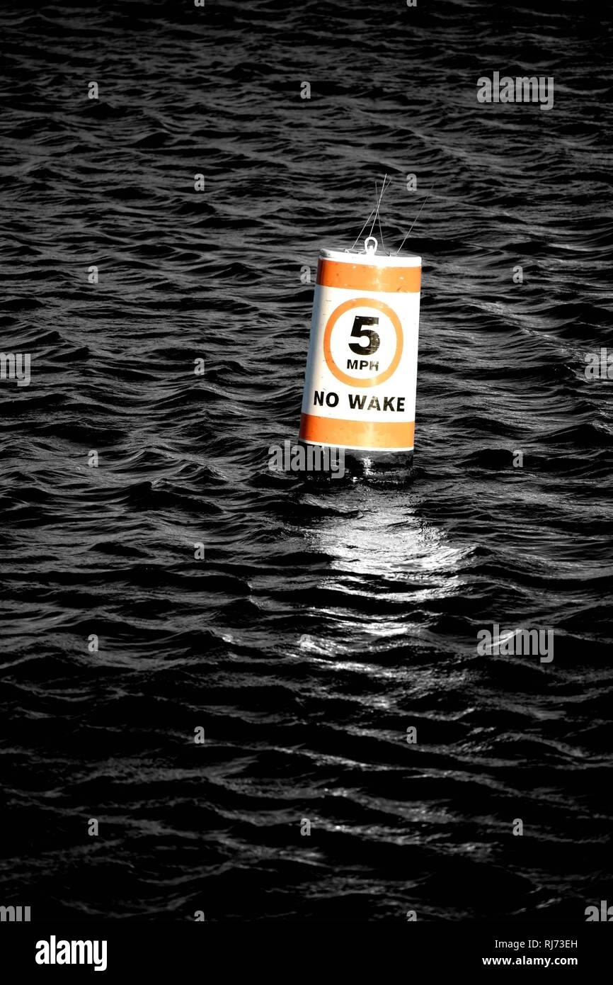Eine Signalboje mit Geschwindigkeitsbegrenzung abstrakt gewelltem schwimmt in Wasser, Stockbild