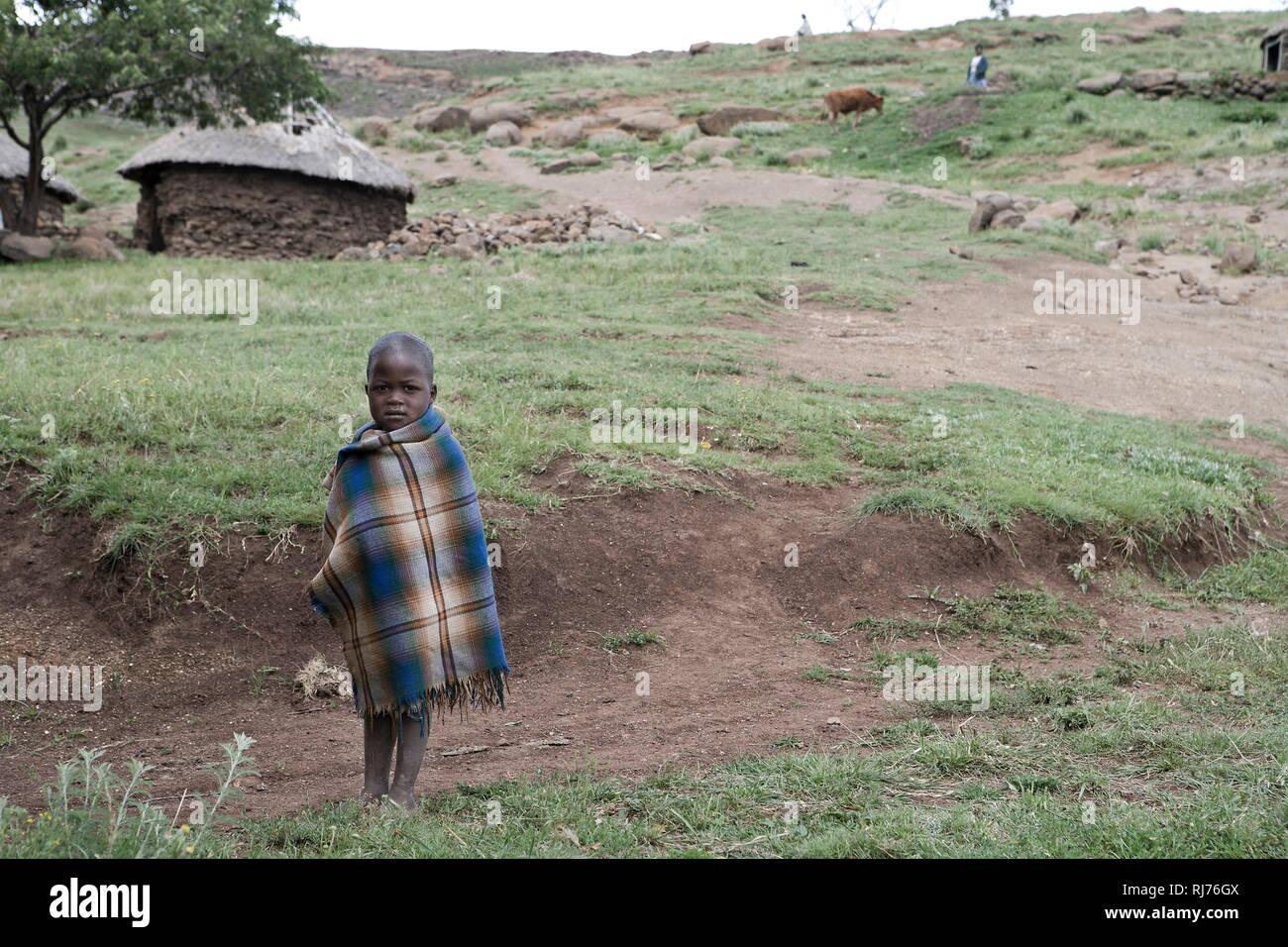 Kleiner Junge in Decke gehüllt vor einer Steinhütte Stockbild