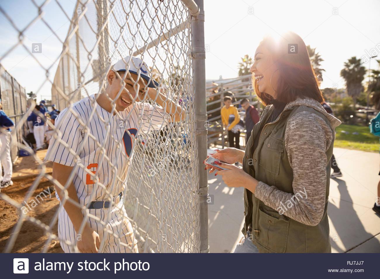 Happy Latinx Baseballspieler im Gespräch mit Freundin am sonnigen Zaun Stockbild