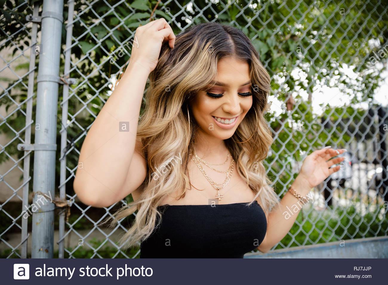 Sorglos, glücklich, Latinx junge Frau lehnte sich gegen Zaun Stockbild