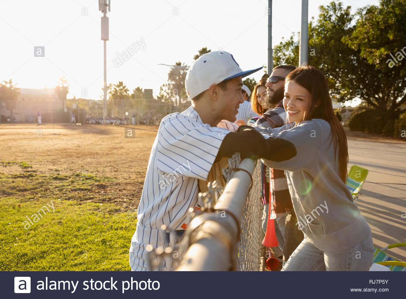 Baseballspieler im Gespräch mit Freundin am sonnigen Zaun Stockbild