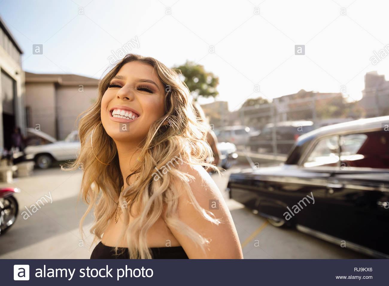 Lachen, Latinx unbeschwerte junge Frau im sonnigen Parkplatz Stockbild