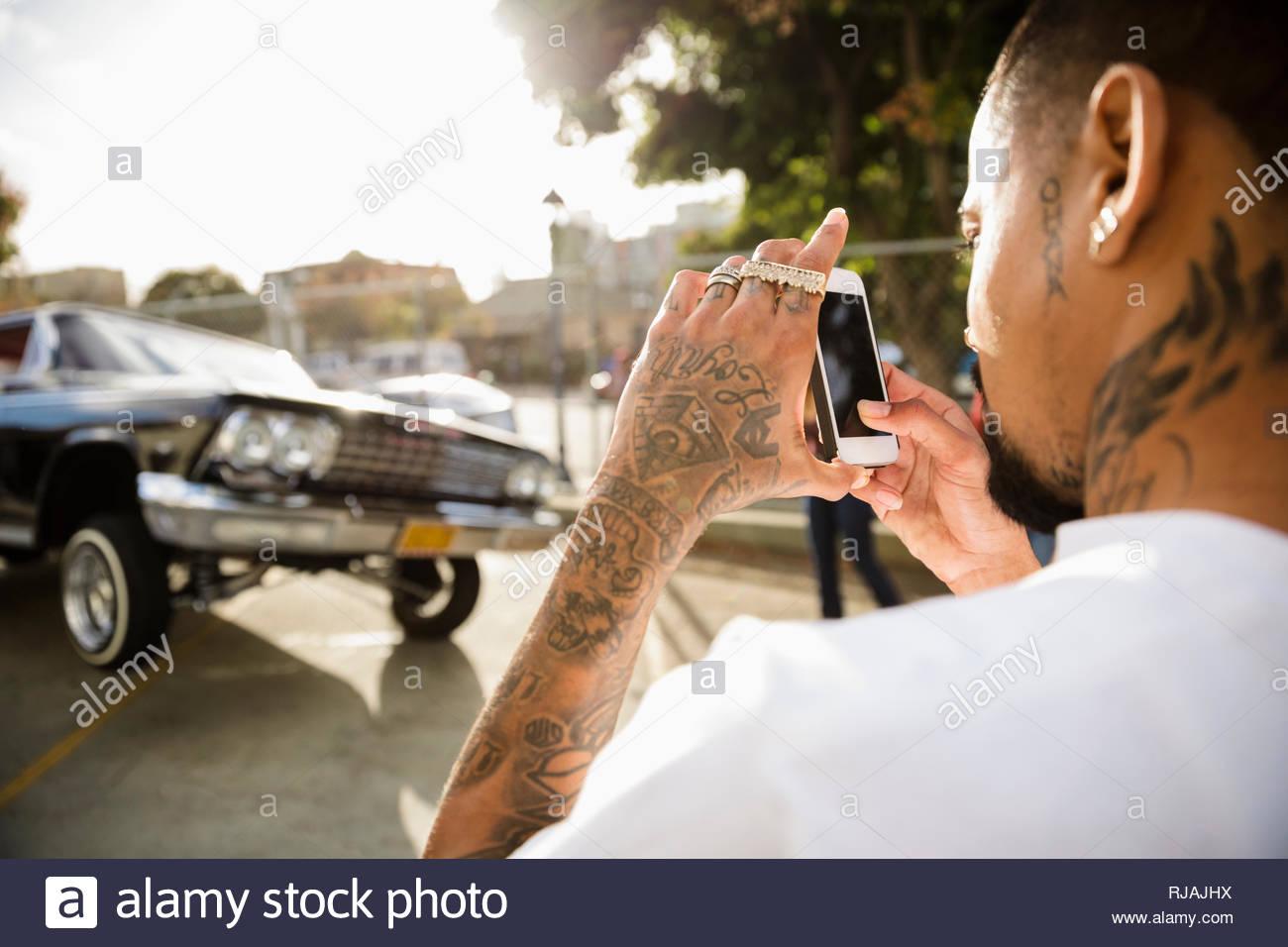 Latinx Mann mit Tattoos fotografieren Low Rider Auto springen in Parkplatz Stockbild