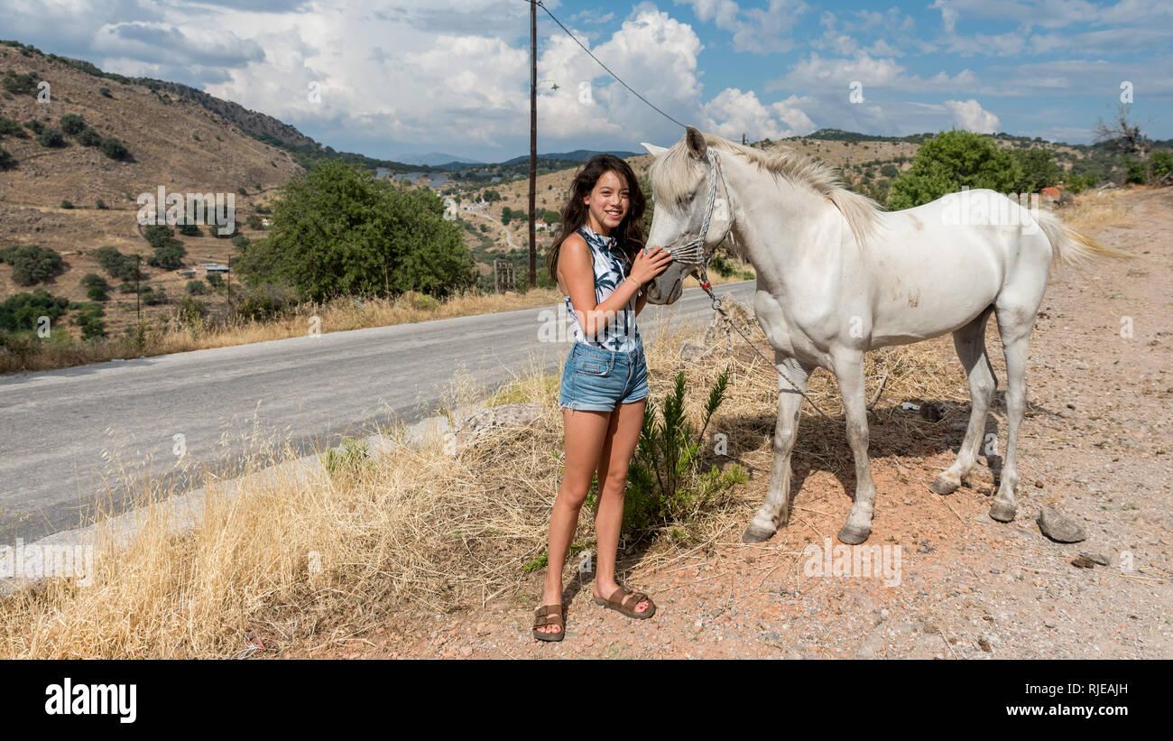 Junge jugendlich Mädchen mit weißen Pferd auf der Seite der Straße Stockbild