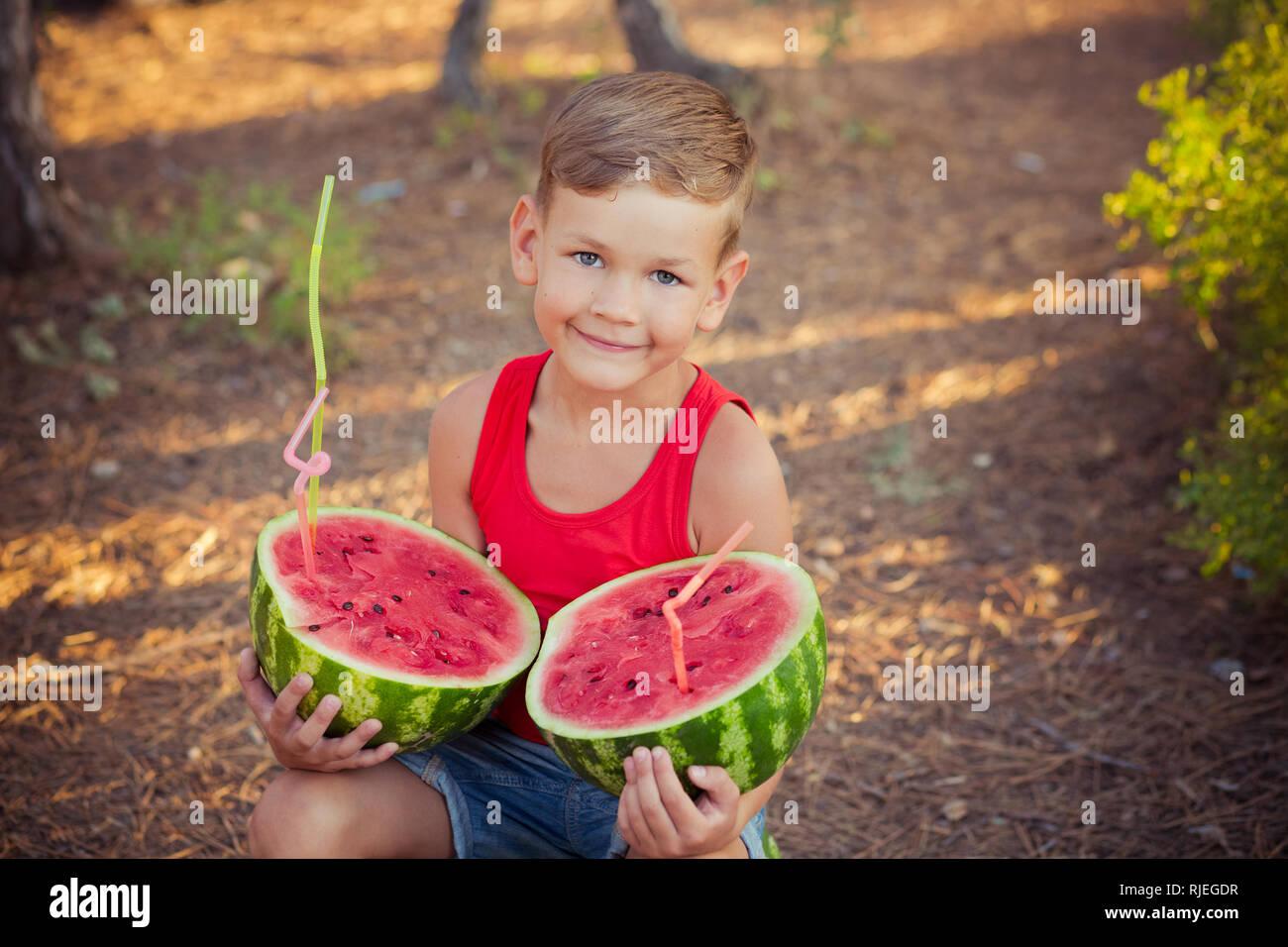 Schöner junge Kind im Central Park Wald Wiese mit Sommer frisch saftig rot grün Wassermelone mit Kunststoff cocktail Stroh posieren. Stockfoto