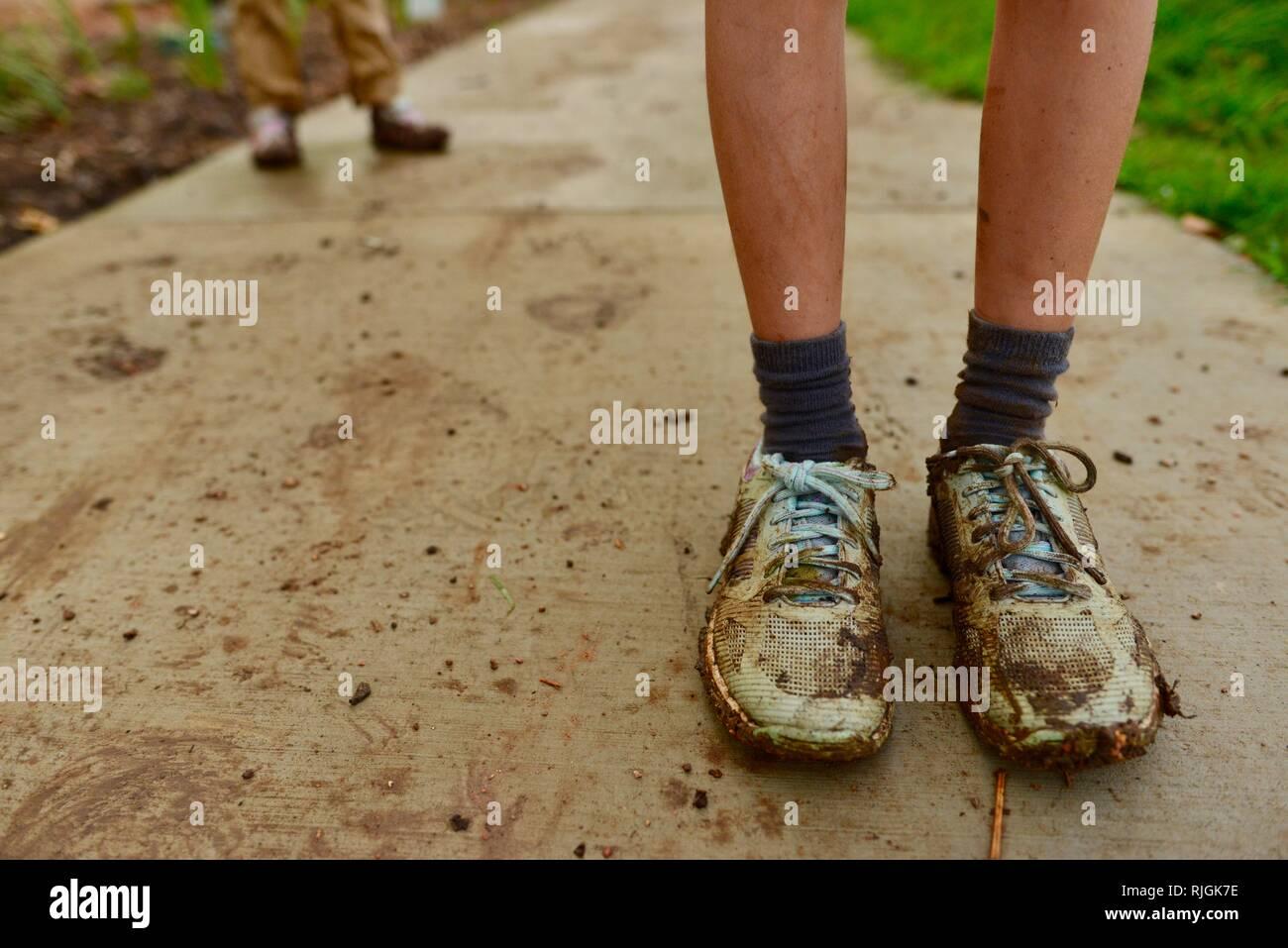 Schlammigen Schuhen auf junge Kinder im schulpflichtigen Alter nach einem Spaziergang entlang einem Feldweg, Moongun Wanderweg am Elliot Federn, Townsville, Queensland, Australien Stockfoto