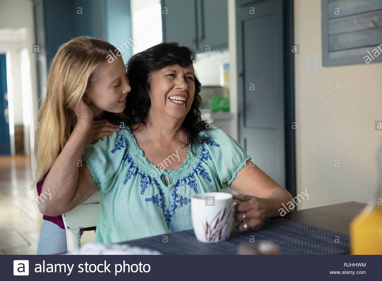 Herzlichen Latinx Enkelin und Großmutter an den Küchentisch Stockbild