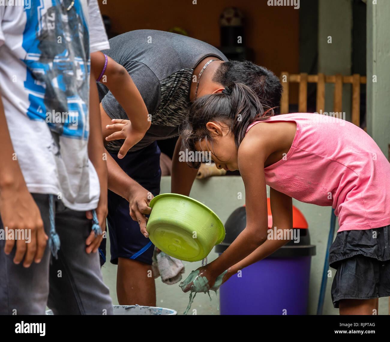 Latin kind Waschen der Hände mit Schaufel in Guatemala Stockfoto