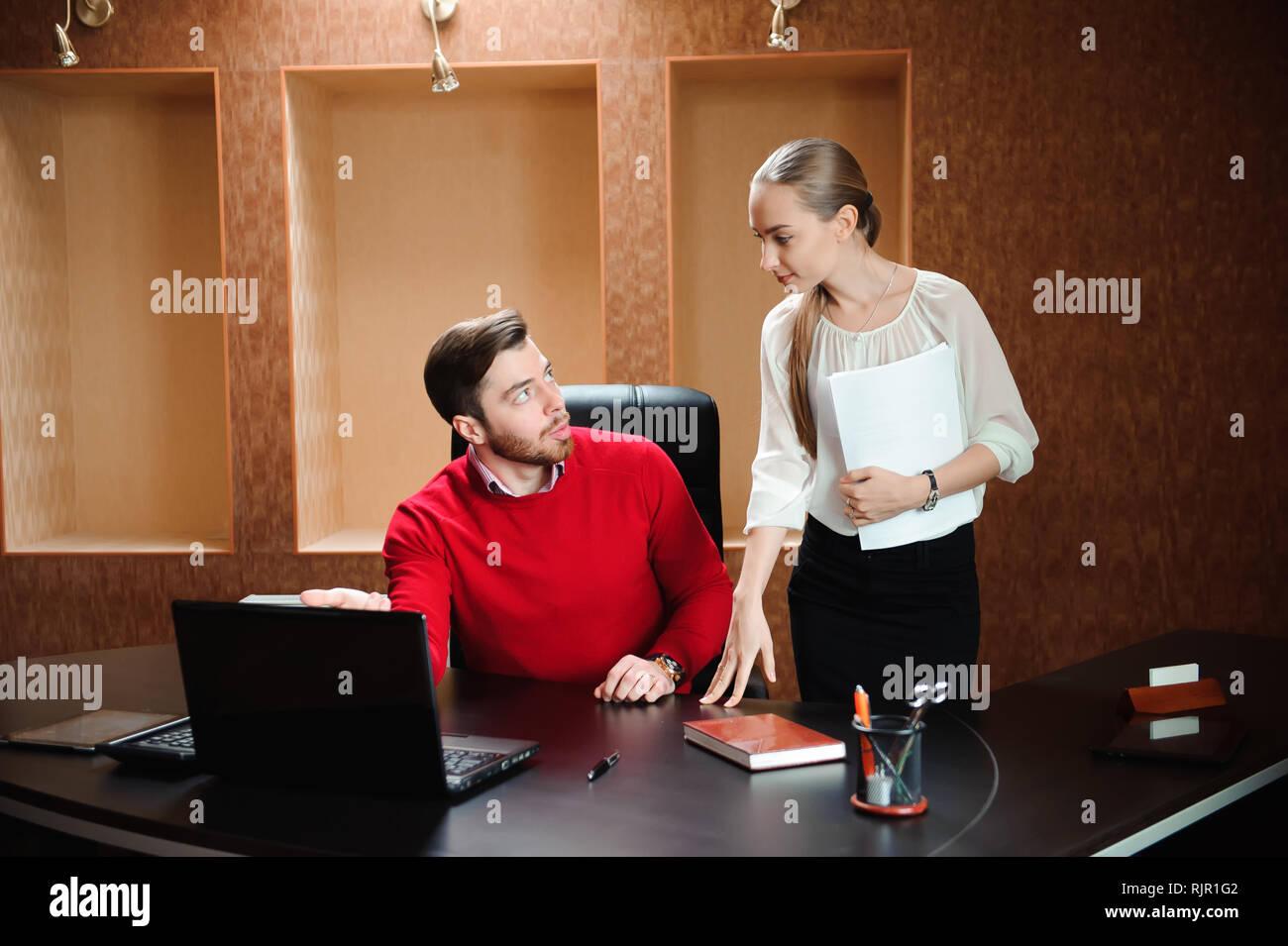 Zuversichtlich Boss mit Papier erklärt etwas zu Sekretär in t Stockfoto