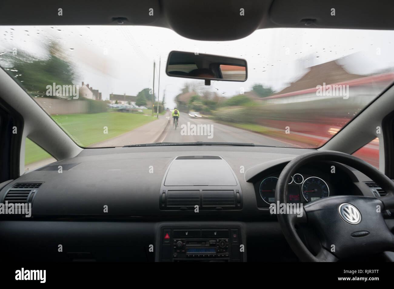 Rennradfahrer tragen hohe Sichtbarkeit Jacke zeichnet sich bei Besetzt country lane, die Kraftfahrer ausreichend Zeit zu reagieren. Stockfoto
