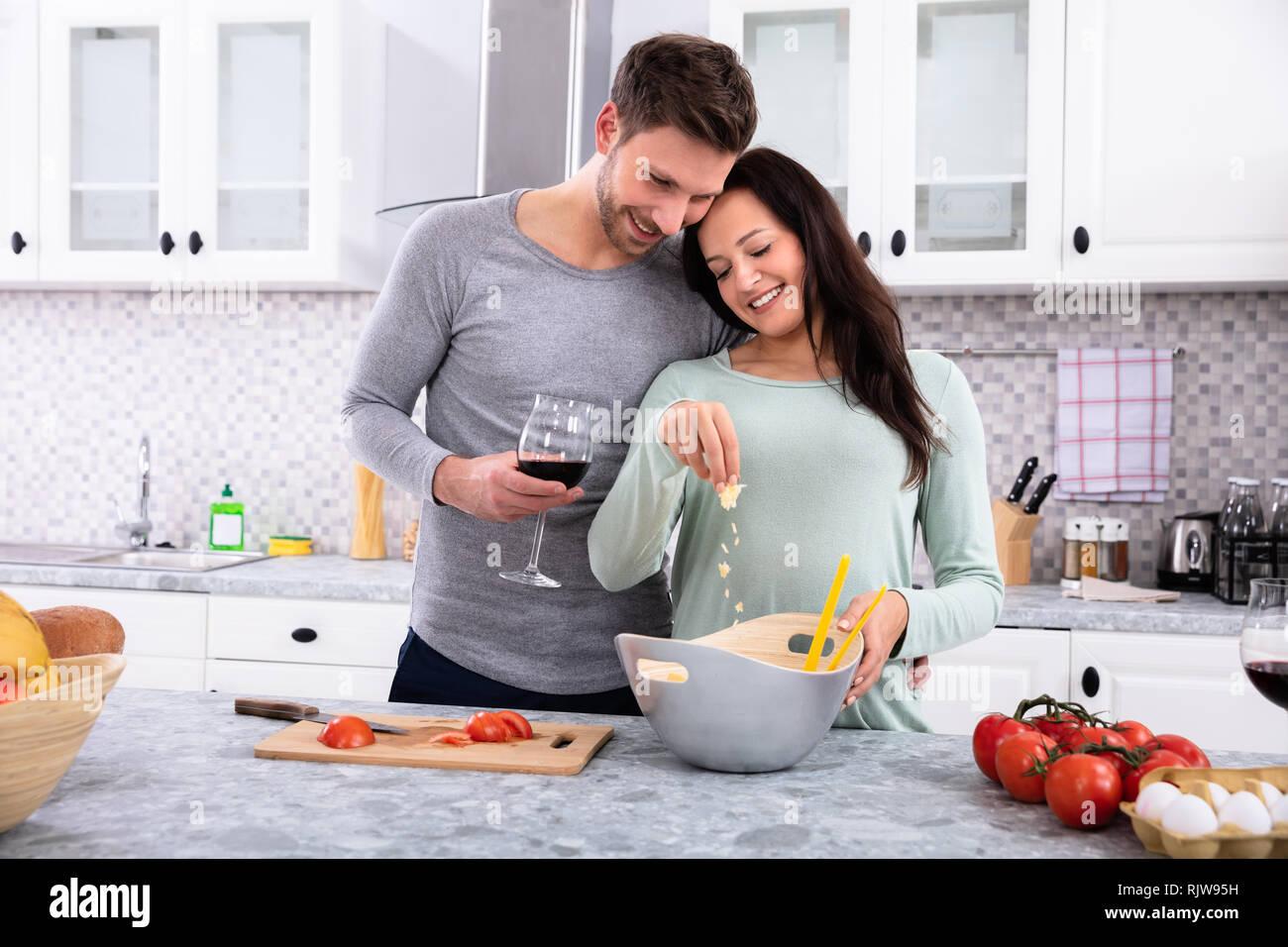 Lächelnde Frau Besprühen die Butter, die mit ihrem Mann in der Küche Holding Wein Glas Stockfoto
