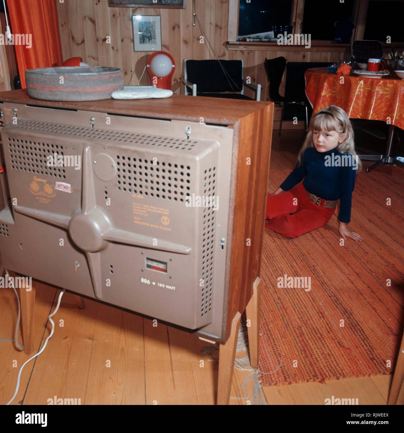 Fernsehen in den 1960er Jahren. Ein Mädchen sitzt vor einem Fernseher mit ihren Augen auf dem Bildschirm und das Programm gesetzt. Schweden 1969 Stockfoto