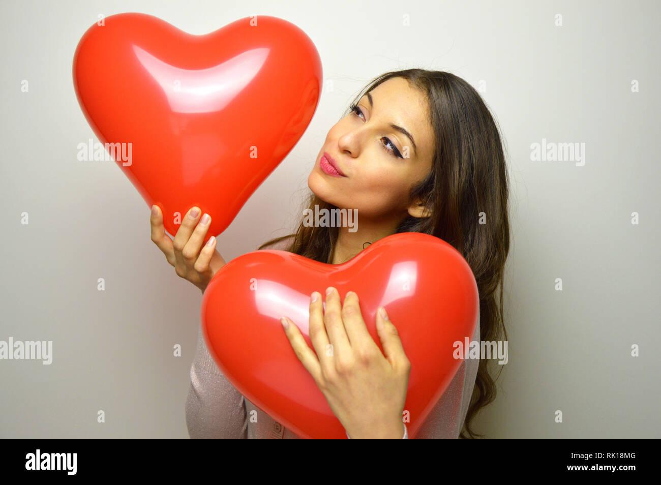 Valentinstag Konzept. Schöne Mädchen küssen herzförmige Ballons und andere in ihren Arm auf grauem Hintergrund. Stockfoto