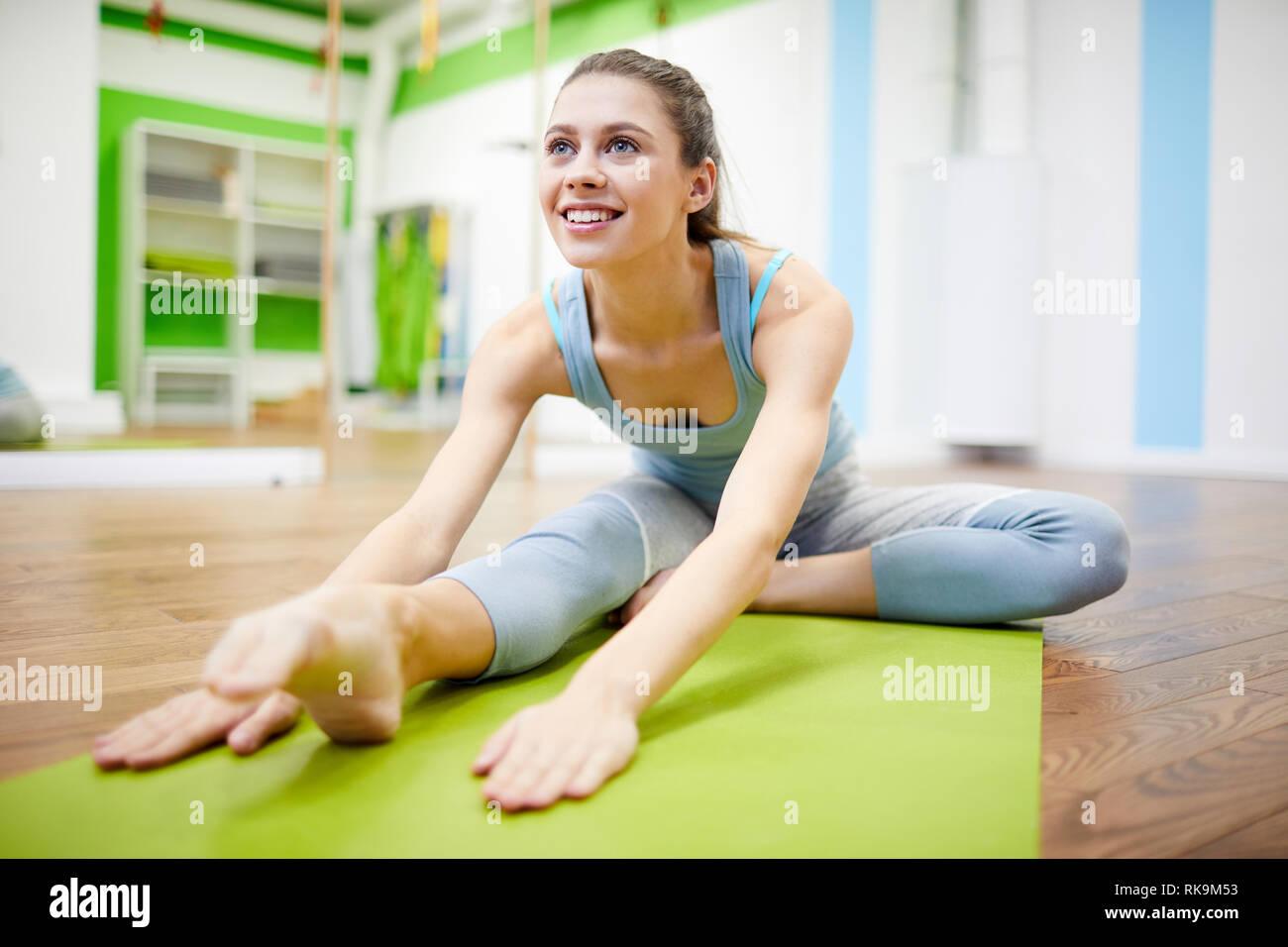 Junge Frau Dehnen in Fitness Club Stockfoto