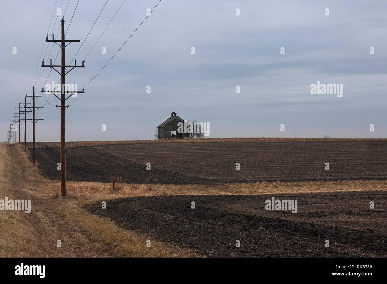 In einer kalten, bewölkten Tag im Herbst, Telefonmasten in eine verdorrte Scheune. Th Scheune, die vor kurzem in gepflügten Feldern steht, ist die einzige stru Stockbild
