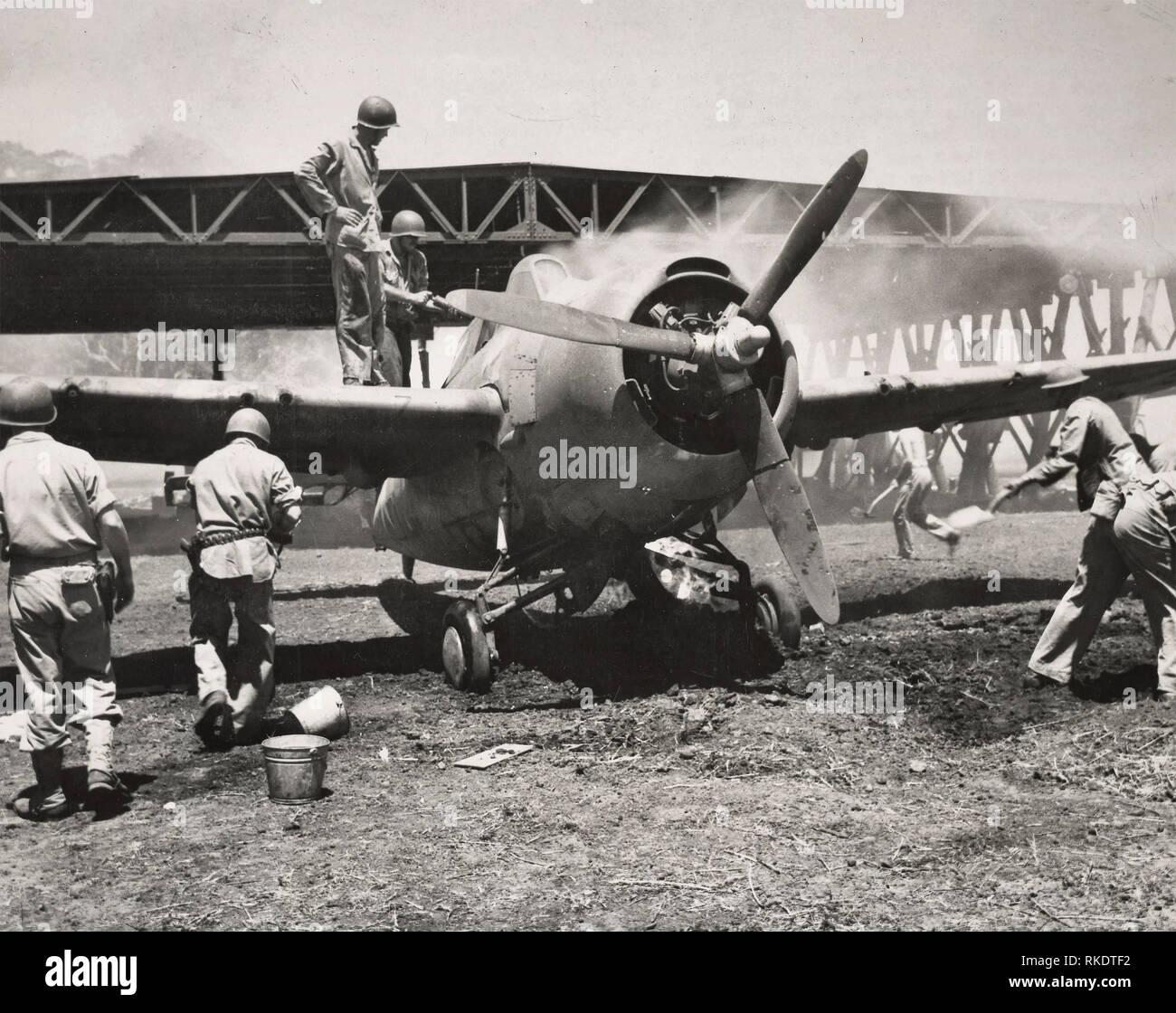 Marine Kampfflugzeug gespeichert. Frißt durch eine japanische Bombe getroffen auf dem Bügel im Hintergrund, diese Marine fighter Plan wurde in den offenen gezogen von Leatherneck, Schmutz und Chemikalien, die Flammen zu löschen. Das Flugzeug, eine Grumman â ? oeWildcatâ ? nicht schwer beschädigt worden war und in der Lage war, in die Luft zu kommen. Das Bild wurde kurz nach der Marines eine strategische Guadalcanal Flughafen aus der Japanischen erfasst. 1942 Stockbild