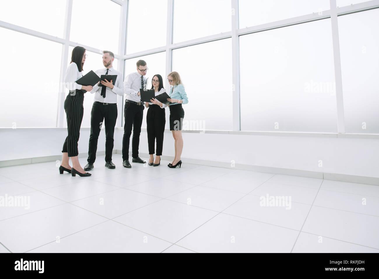 Diskutieren Mitarbeiter geschäftliche Dokumente in der Lobby stehend Stockfoto